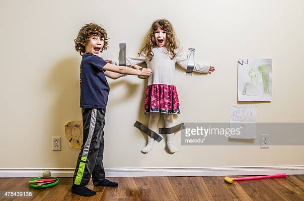 brother hung her sister on the wall - zus stockfoto's en -beelden