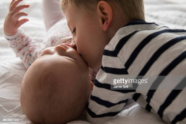 Brother kissing little sister (18-23 months, 4-5) with love