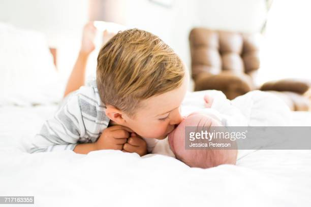 Brother (4-5) lying on bed and kissing sister (0-1 months)