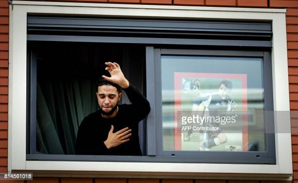 TOPSHOT Brother of Dutch midfielder Abdelhak Nouri Mohammed thanks fans out of the window of the house of Abdelhak Nouri on July 14 2017 in Amsterdam...