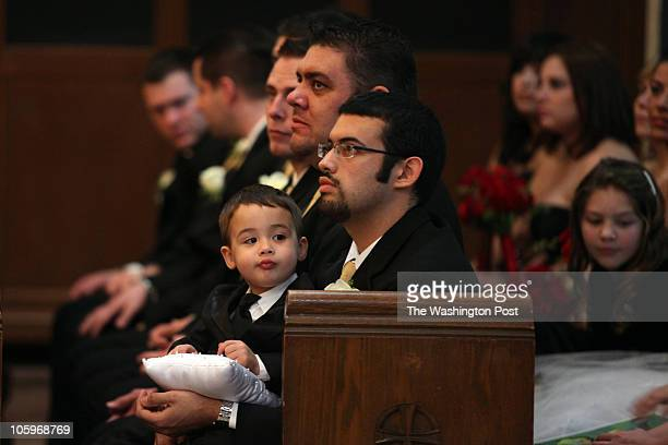 Brother of the bride Marvin Diaz holds his son Viggo during the wedding ceremony of Stephanie Diaz and Brian Hicks at St Anthony of Padua Catholic...