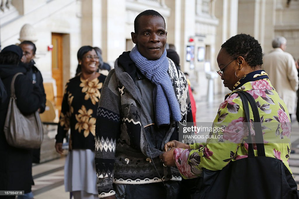 Brother of the late Firmin Mahe, Dahou Koulai Jacques (C) stands outside court in Paris on December 4, 2012 during the trial of four French former soldiers, including a colonel, for killing a man in Ivory Coast in 2005 during a peacekeeping mission in the west African country. The accused say they acted under orders to kill Firmin Mahe, who was suffocated to death while travelling in a French military vehicle. Mahe's death on May 13, 2005, led to the sacking of General Henri Poncet, who was in command of the 4,000-strong peacekeeping mission. AFP PHOTO / Francois GUILLOT