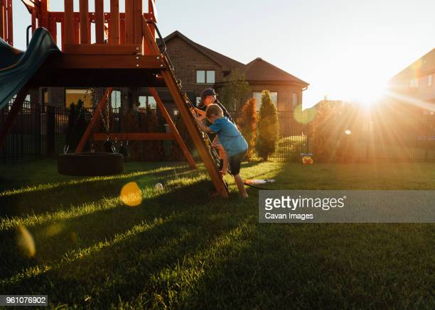 brother playing on slide in backyard during sunset - spielgerät stock-fotos und bilder