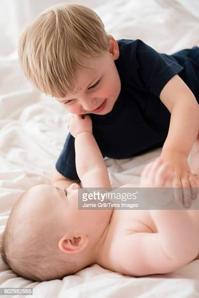 brother (2-3) playing with baby sister (12-17 months) on bed - 12 23 months stock pictures, royalty-free photos & images