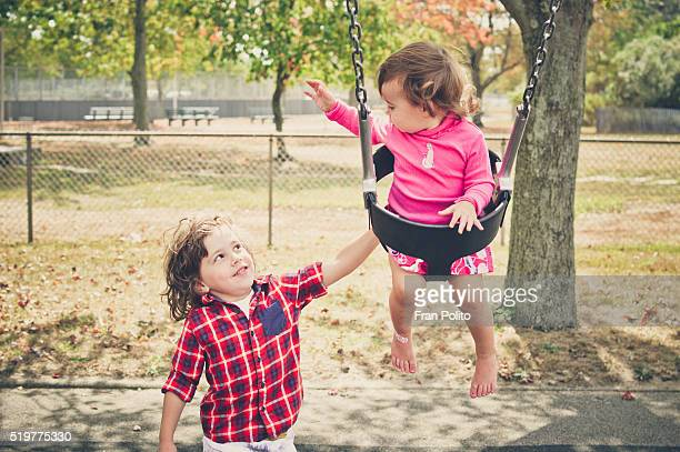 Brother pushing his baby sister on a swing.