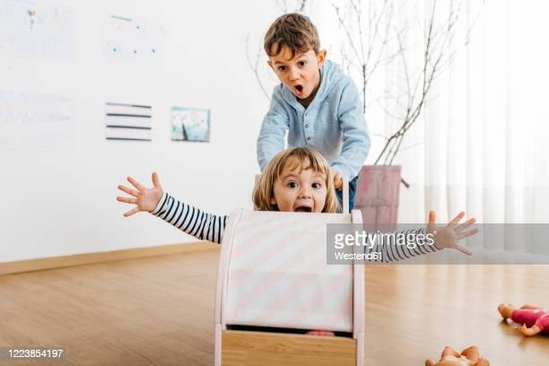 brother pushing sister, sitting in a doll buggy, playing at home - solo bambini foto e immagini stock
