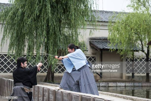 brother, sister dressed as samurai sword fighting in amusement park - resilience stock photos and pictures