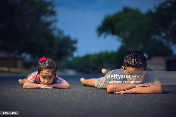 Brother & sister lies prone on the road