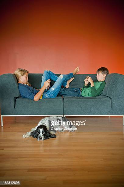 brother &sister on couch with tablet and cell phon