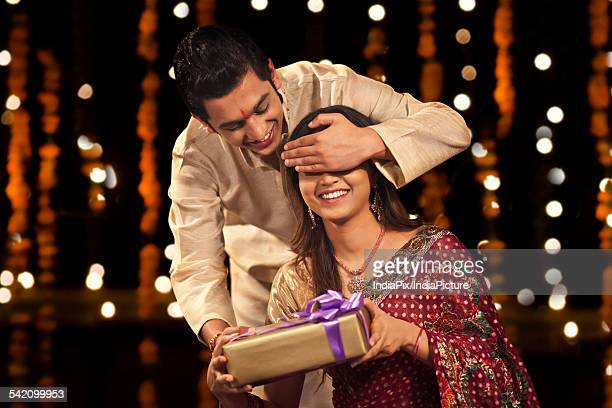brother surprising his sister with a gift - raksha bandhan stock photos and pictures