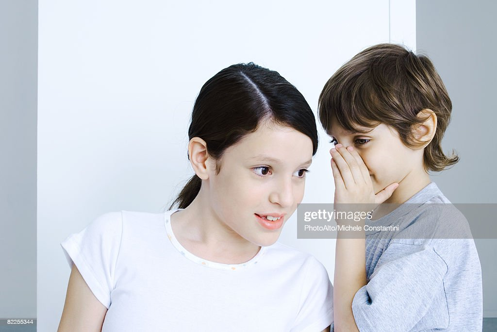 Brother whispering to his sister, hand covering mouth : Stock Photo