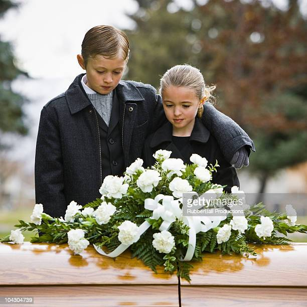 brother with his arm around his sister at a funeral in a cemetery - funeral photos stock photos and pictures