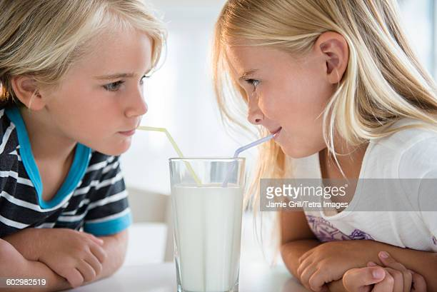 Brother (4-5) with sister (6-7) drinking milk from glass
