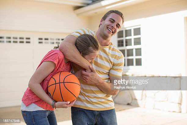 brother with sister in head lock holding basketball - female wrestling holds stockfoto's en -beelden