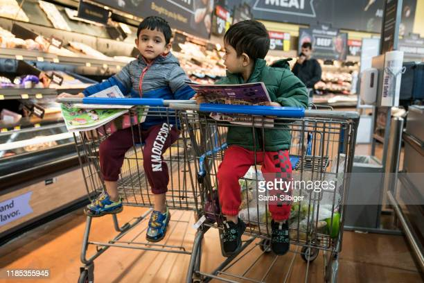 Brothers Abhishreyo Kundu, left, and Avigyan Kundu read the Black Friday circular as they shop with their parents in Walmart on Thanksgiving night...