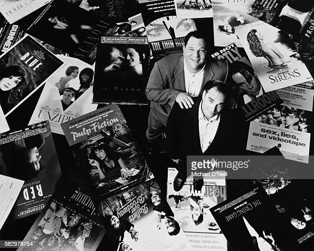 Brothers and cofounders of Miramax Films Bob and Harvey Weinstein are surrounded by posters of Miramax motion pictures