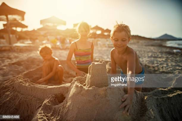 Brothers and sister are building sandcastles on a beach