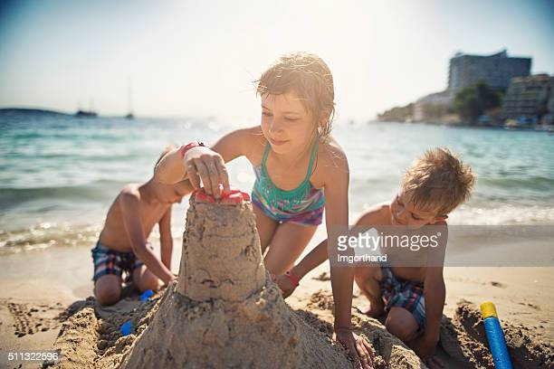 Brothers and sister building a sandcastle on beautiful beach