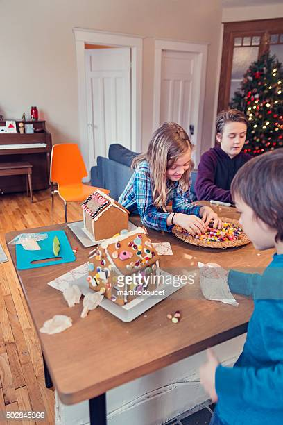 """brothers and sister decorating gingerbread house at christmas time. - """"martine doucet"""" or martinedoucet bildbanksfoton och bilder"""
