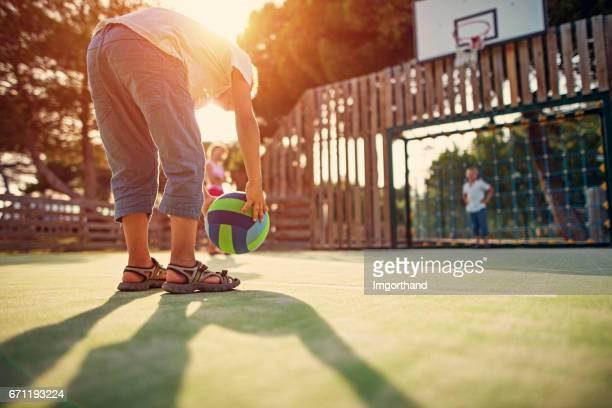 Broers en zus voetballen in het schoolplein