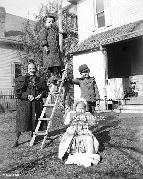 Brothers and sister pose around a tree at home
