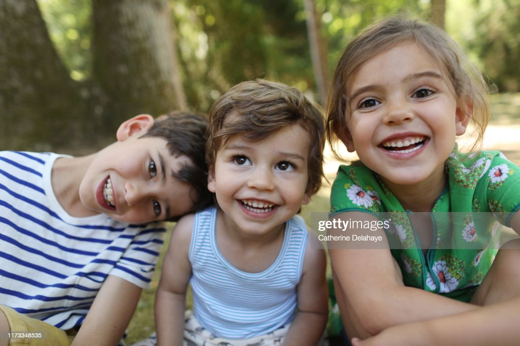 3 brothers and sister posing together in the garden : Foto stock