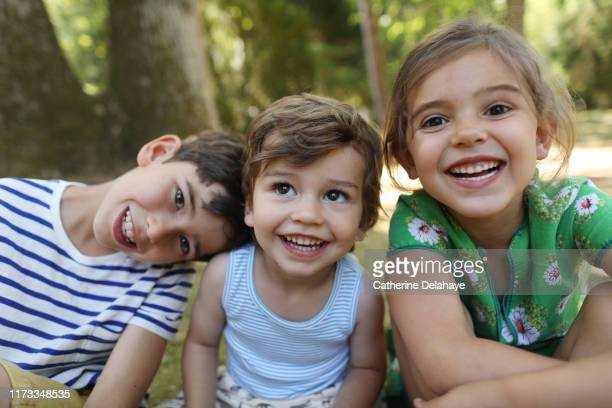 3 brothers and sister posing together in the garden - children only stock pictures, royalty-free photos & images