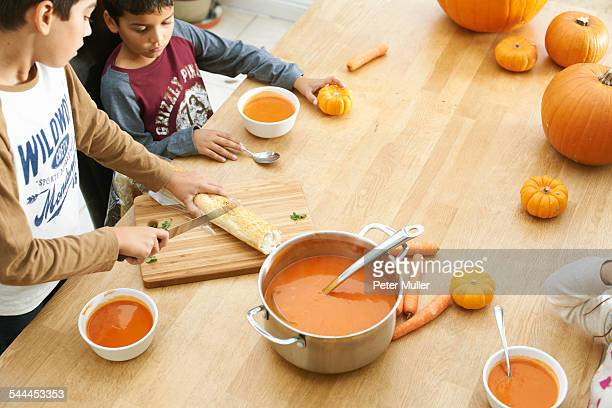Brothers and sister preparing baguette and pumpkin soup in kitchen