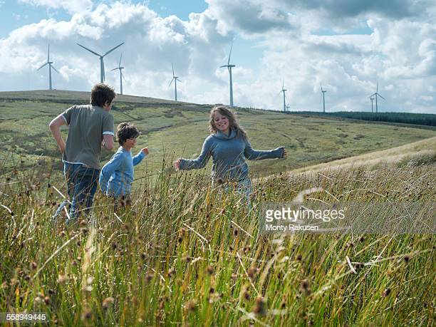 Brothers and sister running in long grass at windfarm