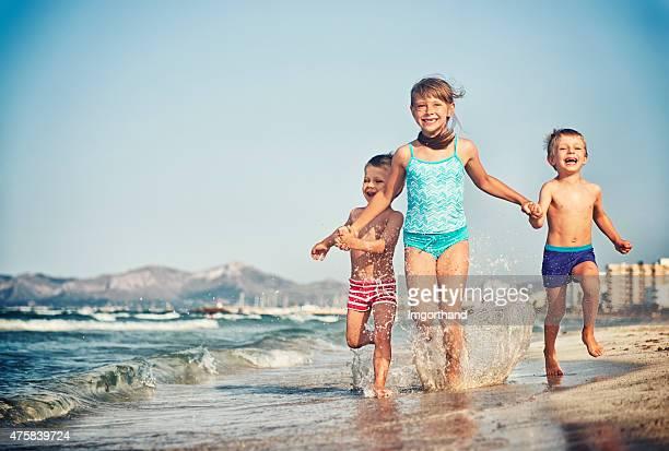 Brüder und Schwester zusammen lachen Laufen am Strand