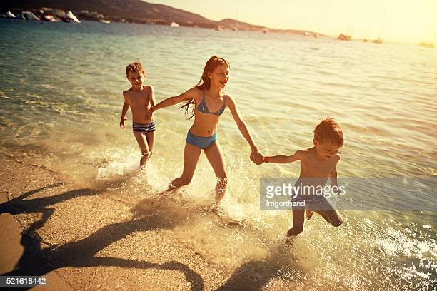 Brothers and sister running on beach laughing