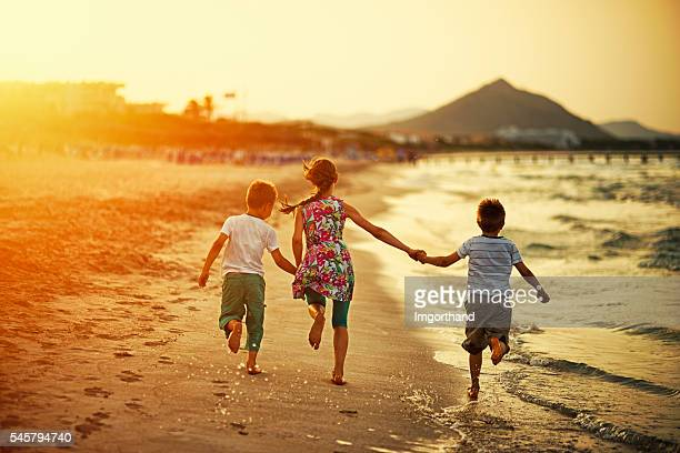 Brothers and sister running on beach on sunset