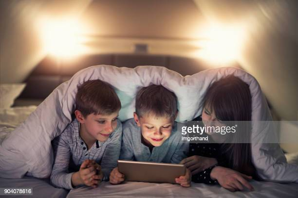 Brothers and sister secretly using tablet