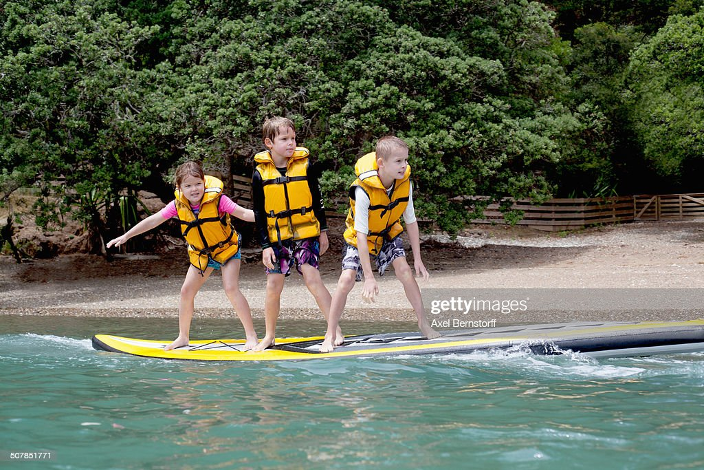 Brothers and sister standing on paddleboard at sea : Stock Photo