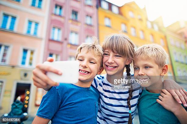 Brothers and sister tourists taking selfie