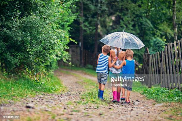 Brothers and sister walking in rain together under one umbrella