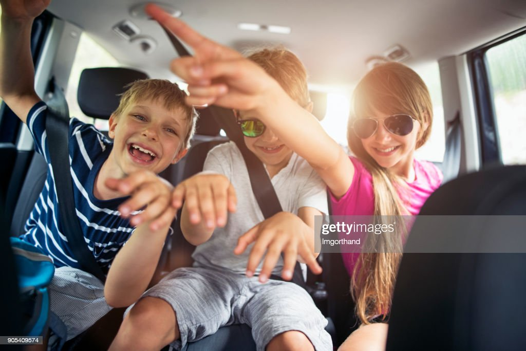 Brothers and sisters enjoying travelling by car : Stock Photo