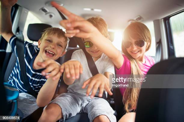 brothers and sisters enjoying travelling by car - family inside car stock photos and pictures
