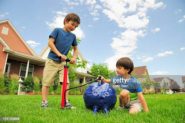 brothers blow up a hopper ball - air pump stock photos and pictures
