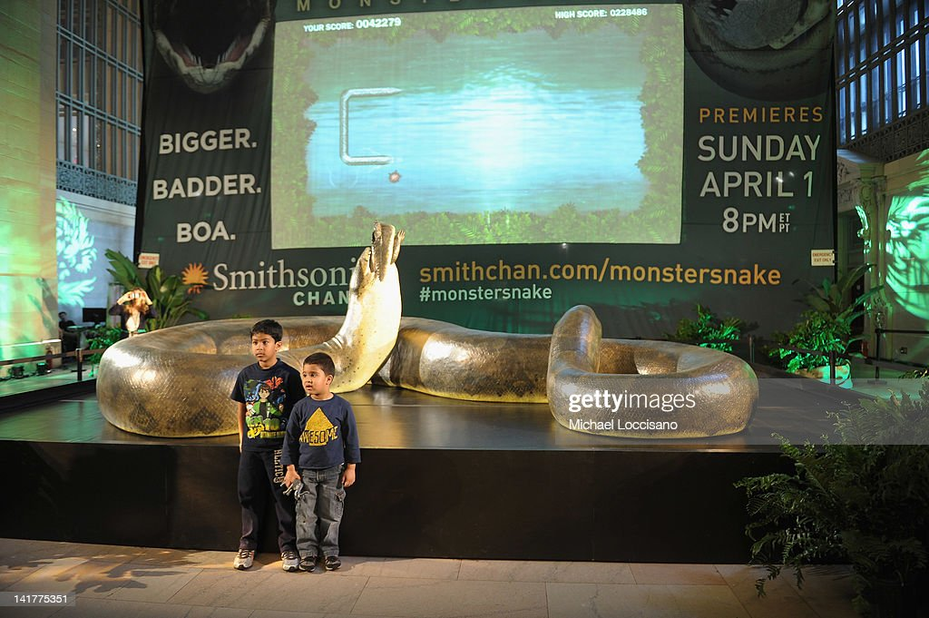 Brothers Christian Mall (L) and Lukas Mall pose in front of a replica of the prehistoric Titanoboa, the largest snake to ever live, on display at Grand Central Terminal on March 23, 2012 in New York City.