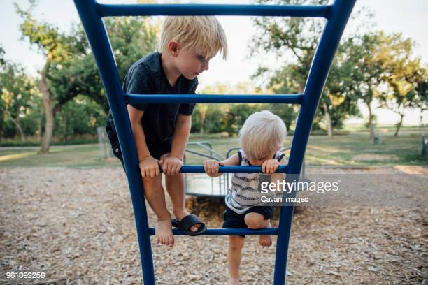 brothers climbing monkey bars at playground - spielgerät stock-fotos und bilder