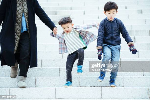 brothers connecting hands with their mothers - yusuke nishizawa stock-fotos und bilder