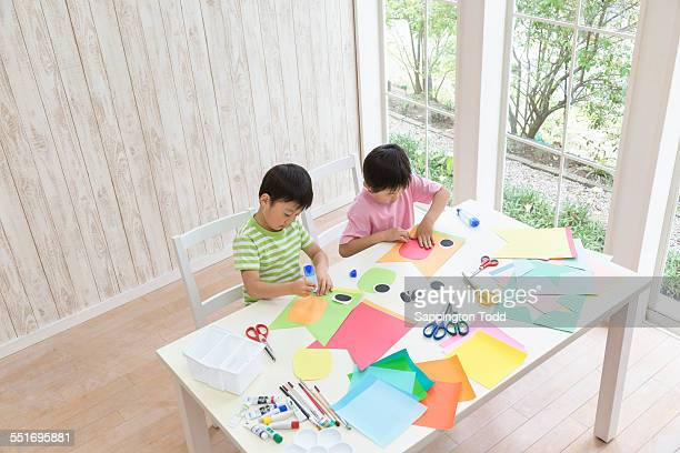 Brothers Doing Craft Activity With Paper And Glue