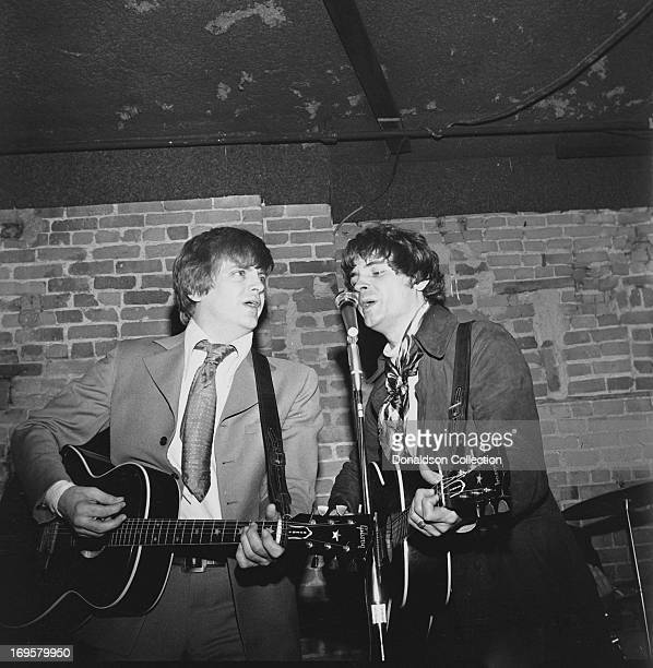 Brothers Don Everly and Phil Everly of the rock and roll group the Everly Brothers perform onstage with their band and their Gibson acoustic guitars...