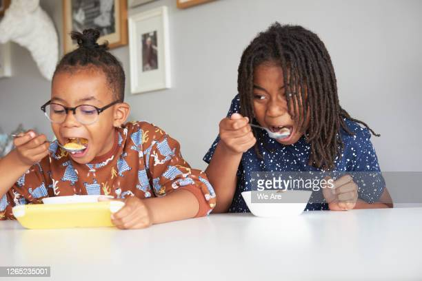 brothers eating cereal and playing video game - togetherness stock pictures, royalty-free photos & images