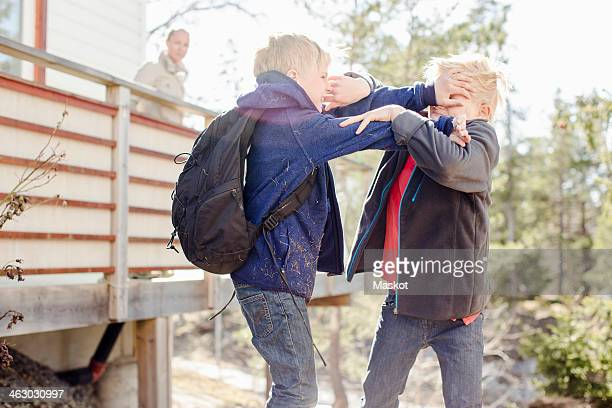 Brothers fighting while mother looking at them from balcony