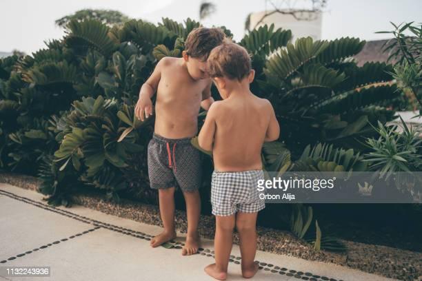 hermanos divirtiéndose en la playa - chico desnudo cuerpo entero fotografías e imágenes de stock
