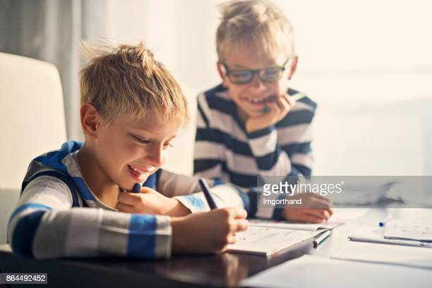 brothers having fun doing homework together - brother stock pictures, royalty-free photos & images