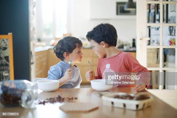 2 brothers having their breakfast - rivaliteit stockfoto's en -beelden