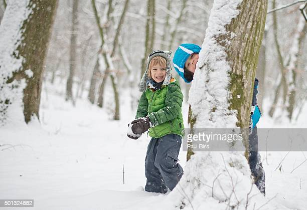 Brothers hiding behind tree trunk about to throw snow ball